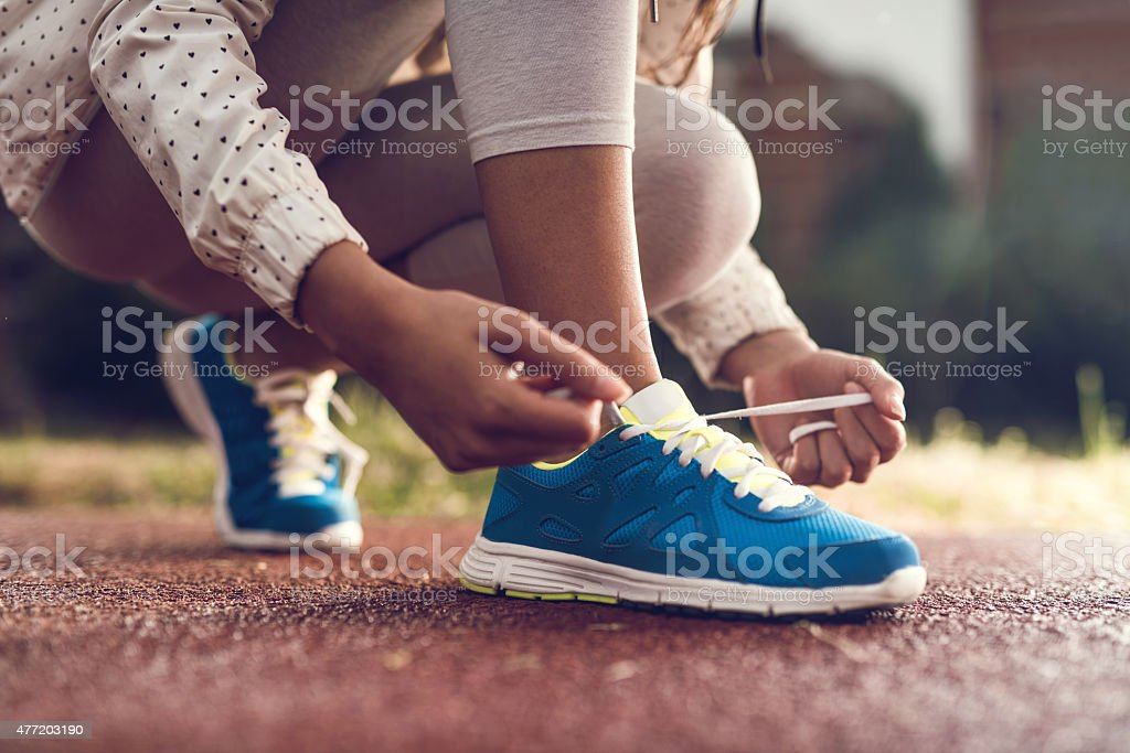 Unrecognizable athlete tying shoelaces on sports sneakers. stock photo