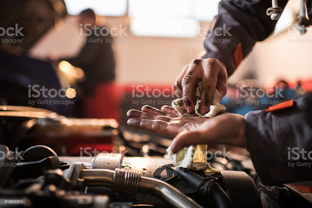 Unrecognizable auto mechanic cleaning his dirty hands. stock photo