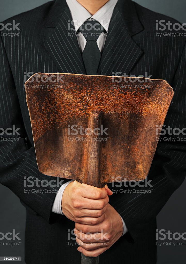 Unrecognizable businessman holding metal shovel stock photo