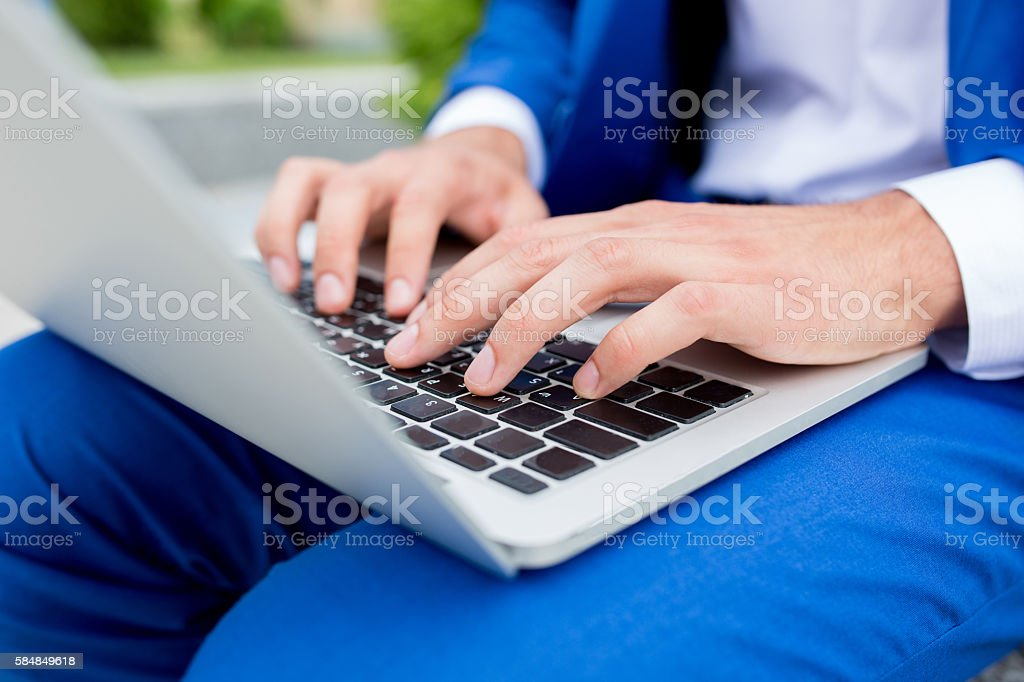 Unrecognizable businessman typing on laptop. stock photo