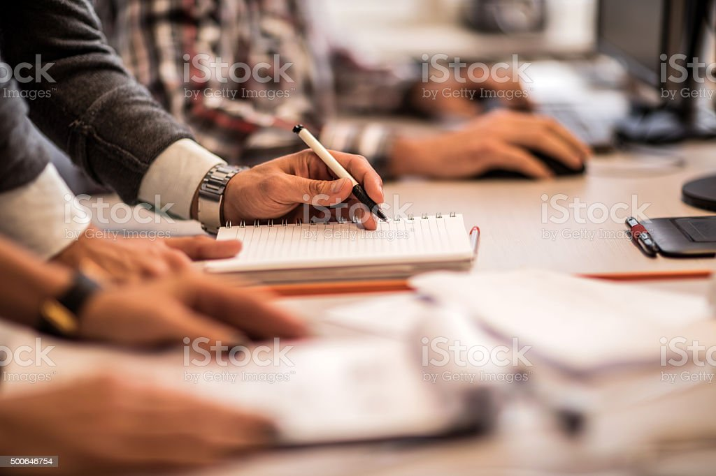 Unrecognizable businessman writing in a notebook in the office. stock photo