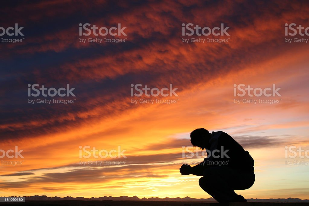 Unrecognizable Caucasian Male Praying Against Dramatic Sunset Sky stock photo
