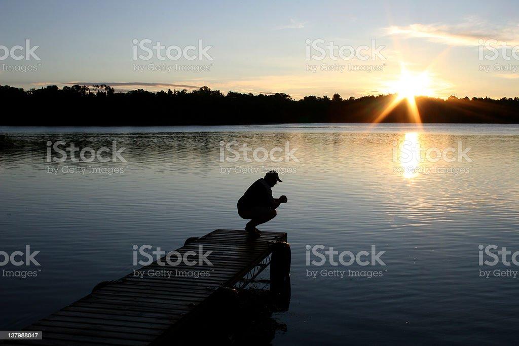 Unrecognizable Caucasian Male Praying By Lake stock photo