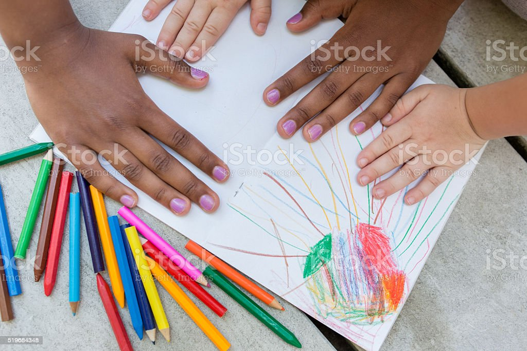 Unrecognizable children's hands on a paper with colorful crayons stock photo