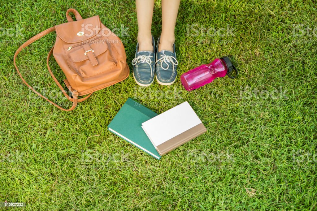 Unrecognizable college student sits in grass on campus stock photo