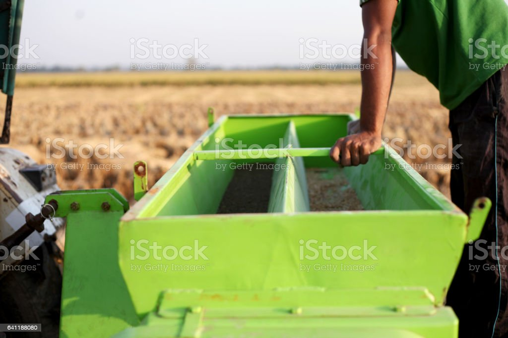 Unrecognizable farmer standing near wheat Sowing Machine stock photo