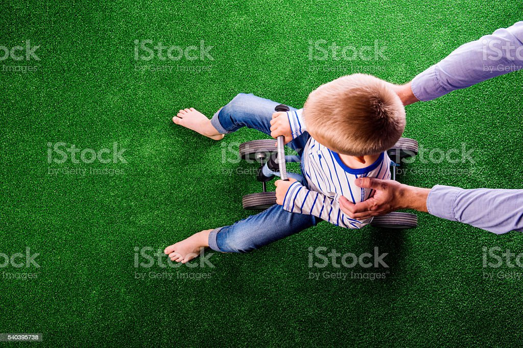 Unrecognizable father holding his son riding a bike stock photo