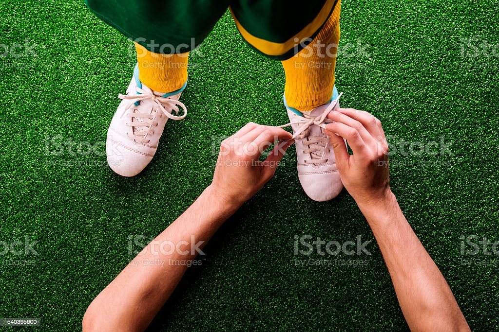 Unrecognizable father tying shoelaces to his son, football stock photo