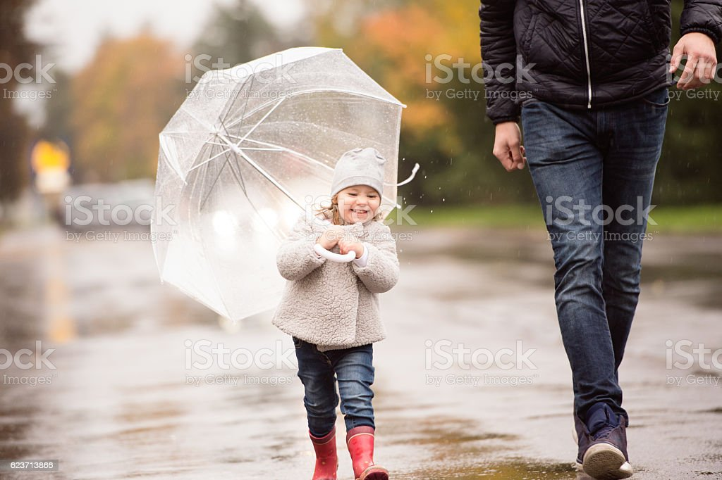 Unrecognizable father with little daughter under the umbrella. R stock photo