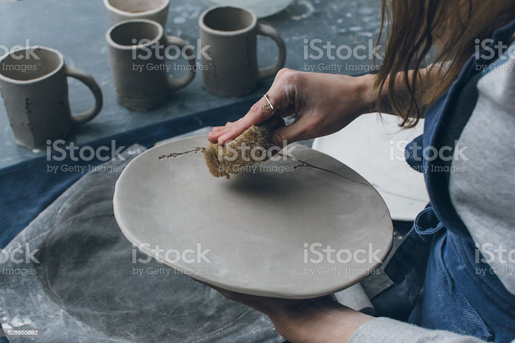 Unrecognizable female potter smoothing dish stock photo
