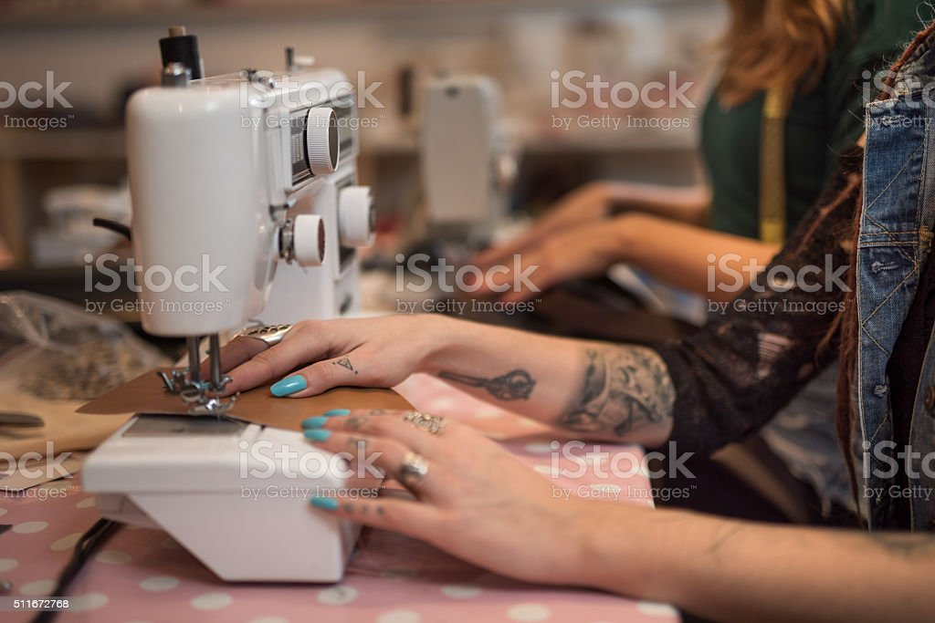 Unrecognizable female tailor sewing on a machine. stock photo