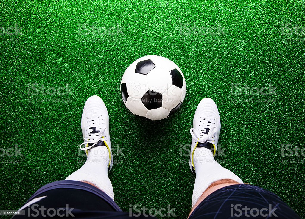 Unrecognizable football player against green grass, studio shot stock photo