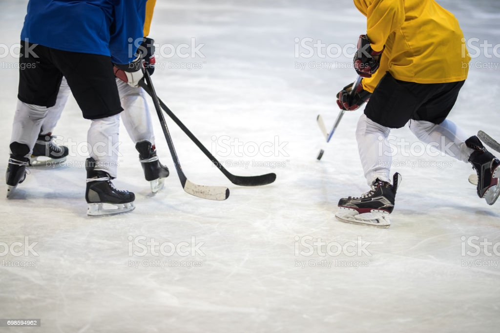 Unrecognizable ice hockey player tackling his rivals on a match. stock photo
