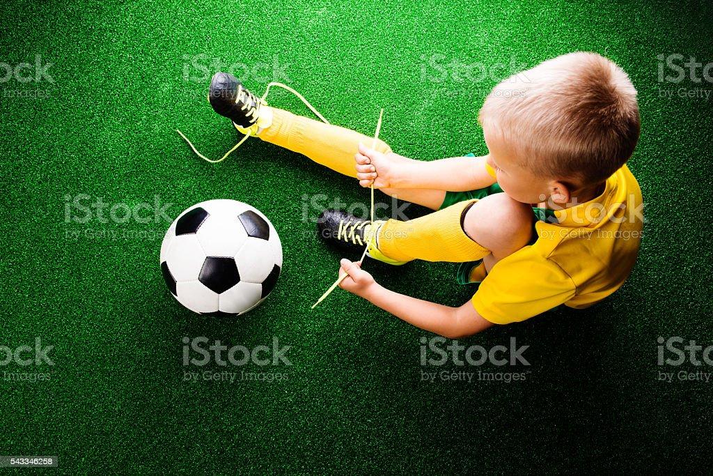 Unrecognizable little football player against green grass, studi stock photo