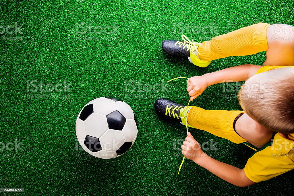 Unrecognizable little football player against green grass, studi stock photo
