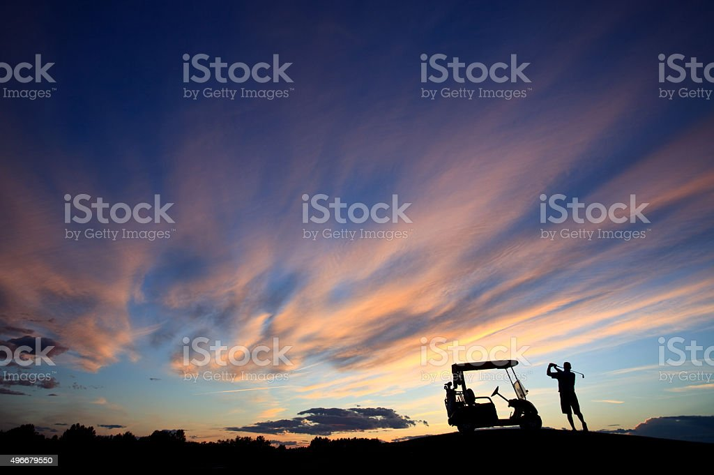 Unrecognizable Male Golfer Swinging by His Golf Cart With Sky stock photo