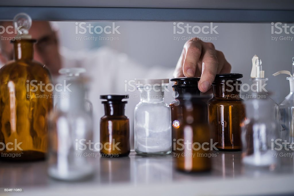 Unrecognizable male scientist choosing the right bottle in laboratory. stock photo
