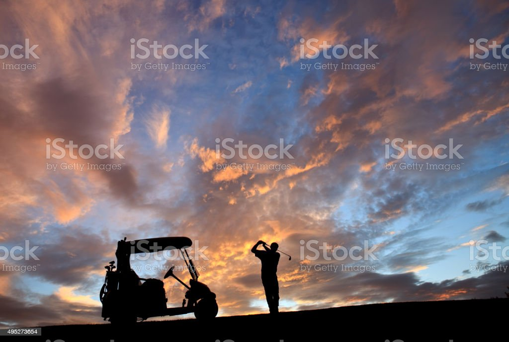 Unrecognizable Male Senior Caucasian Golfer Swinging Against Gorgeous Sunset stock photo