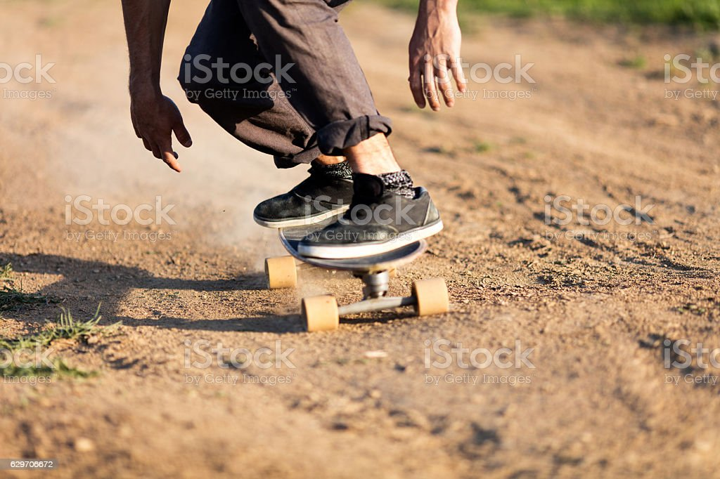 Unrecognizable male skater riding on dirt road. stock photo