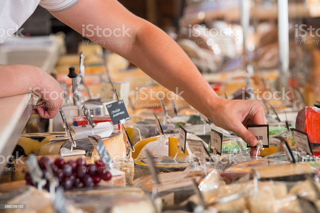 Unrecognizable male supermarket worker with cheese closeup stock photo