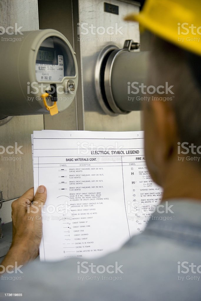 Unrecognizable male wearing hardhat holding paper looking at electrical meter royalty-free stock photo