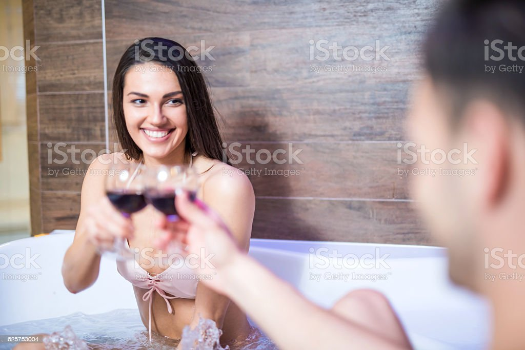 Unrecognizable man cheering with his girlfriend in jacuzzi stock photo