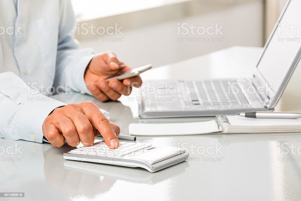Unrecognizable man is working by using a Calculator and phone stock photo