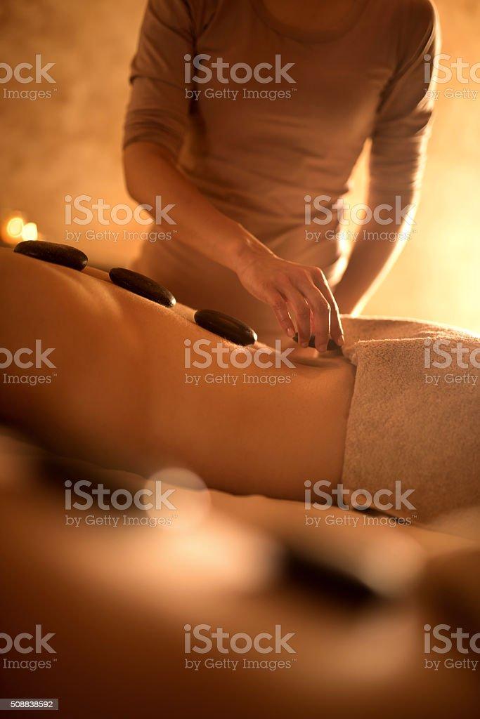 Unrecognizable man receiving lastone therapy at spa. stock photo