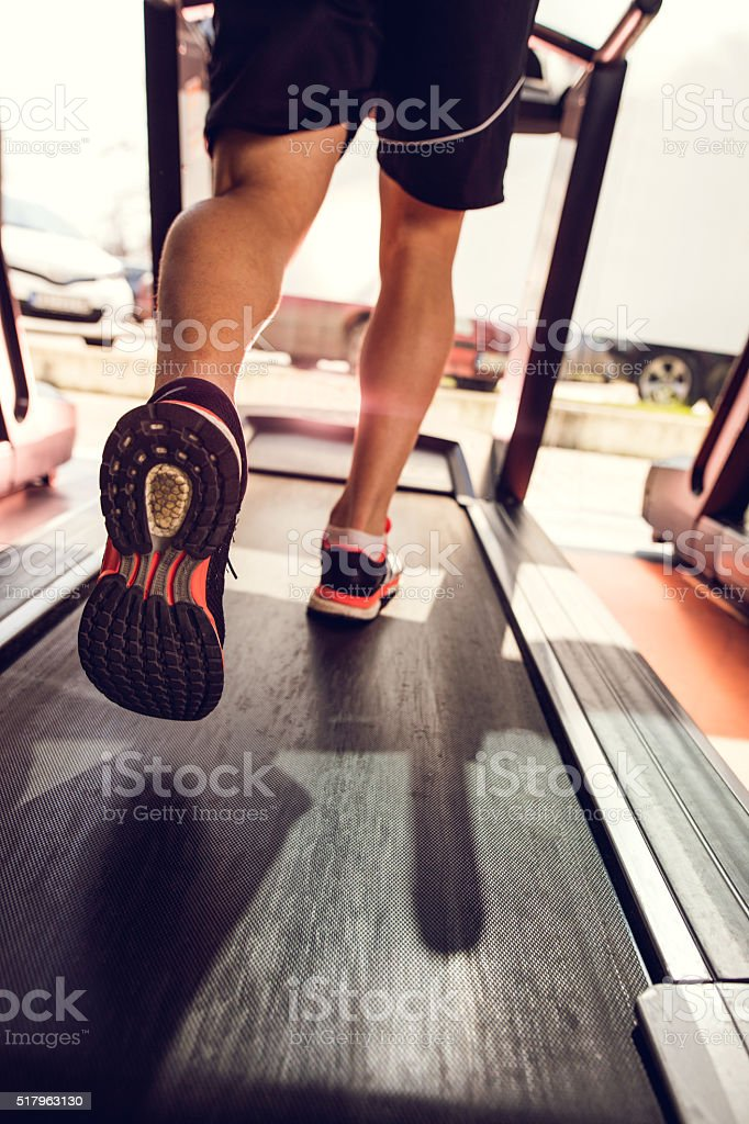 Unrecognizable man running on treadmill in a gym. stock photo