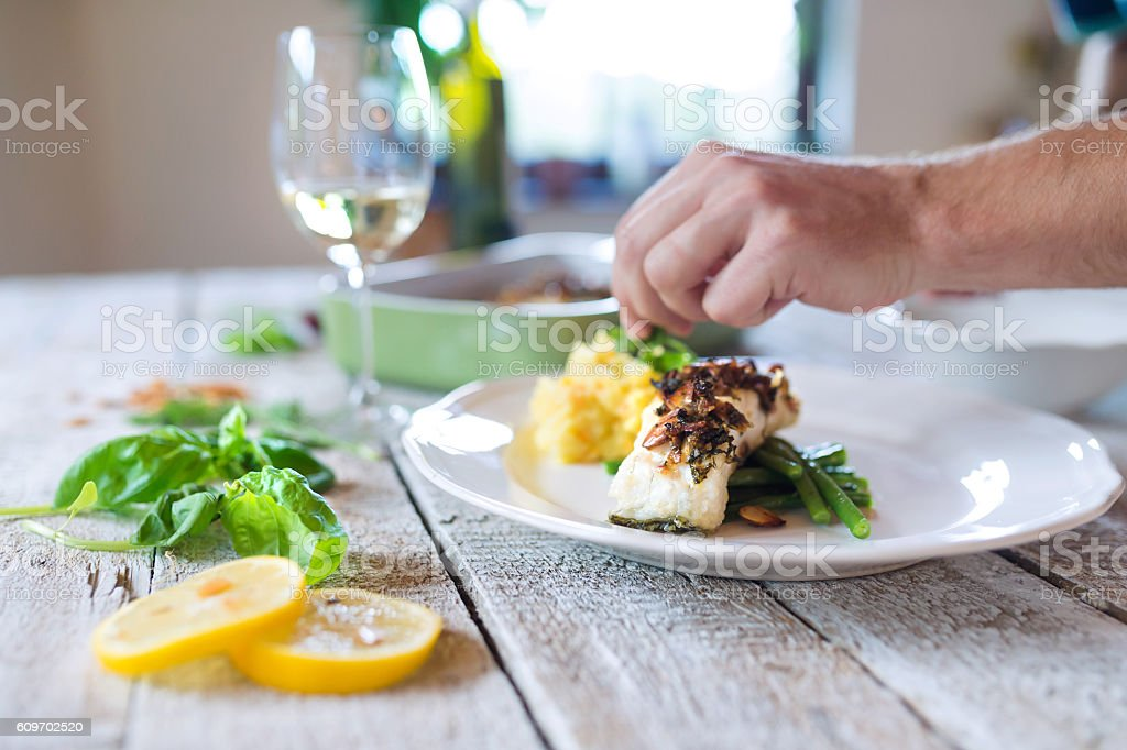 Unrecognizable man serving zander fish fillets on a plate stock photo