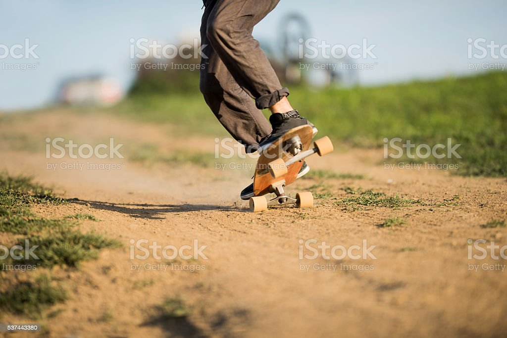 Unrecognizable man skateboarding on a dirt road during the day. stock photo