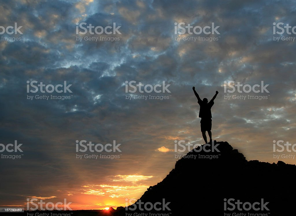 Unrecognizable Man Standing on Mountain Top With Arms Raised stock photo