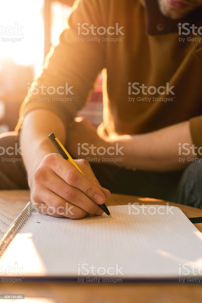 Unrecognizable man taking notes in a textbook. stock photo