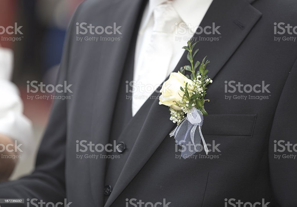 Unrecognizable man with a rose in the buttonhole of his suit royalty-free stock photo