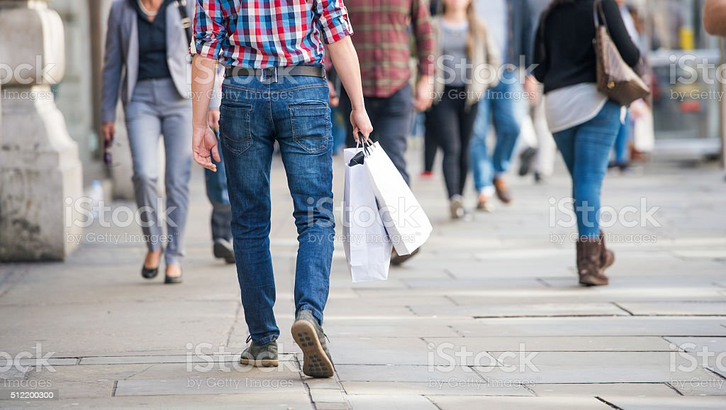 Unrecognizable man with shopping bags in the street, back view stock photo