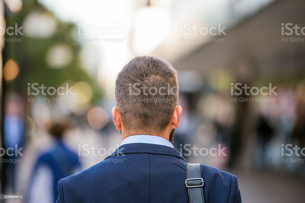 Unrecognizable manager walking in the street, rear view stock photo