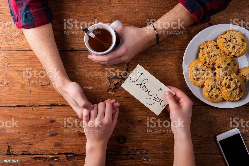 Unrecognizable mans and womans hands. Romantic message. Tea and stock photo