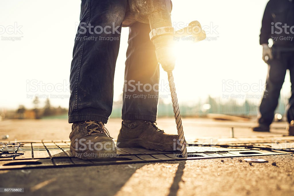 Unrecognizable manual worker using drill on road construction. stock photo