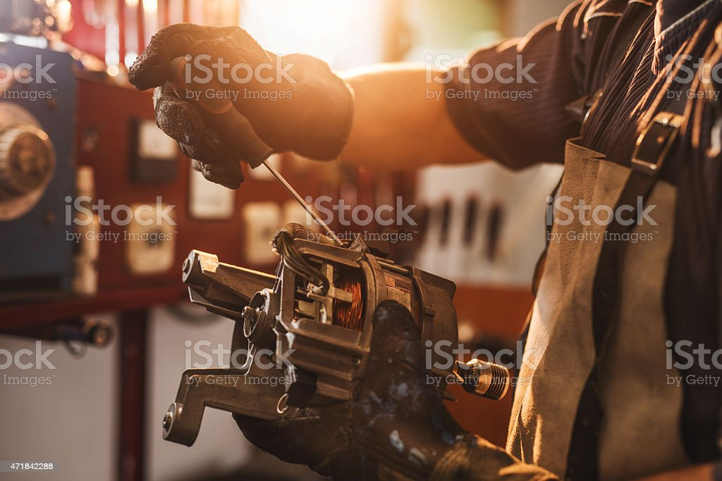 Unrecognizable manual worker working on electric motor. stock photo