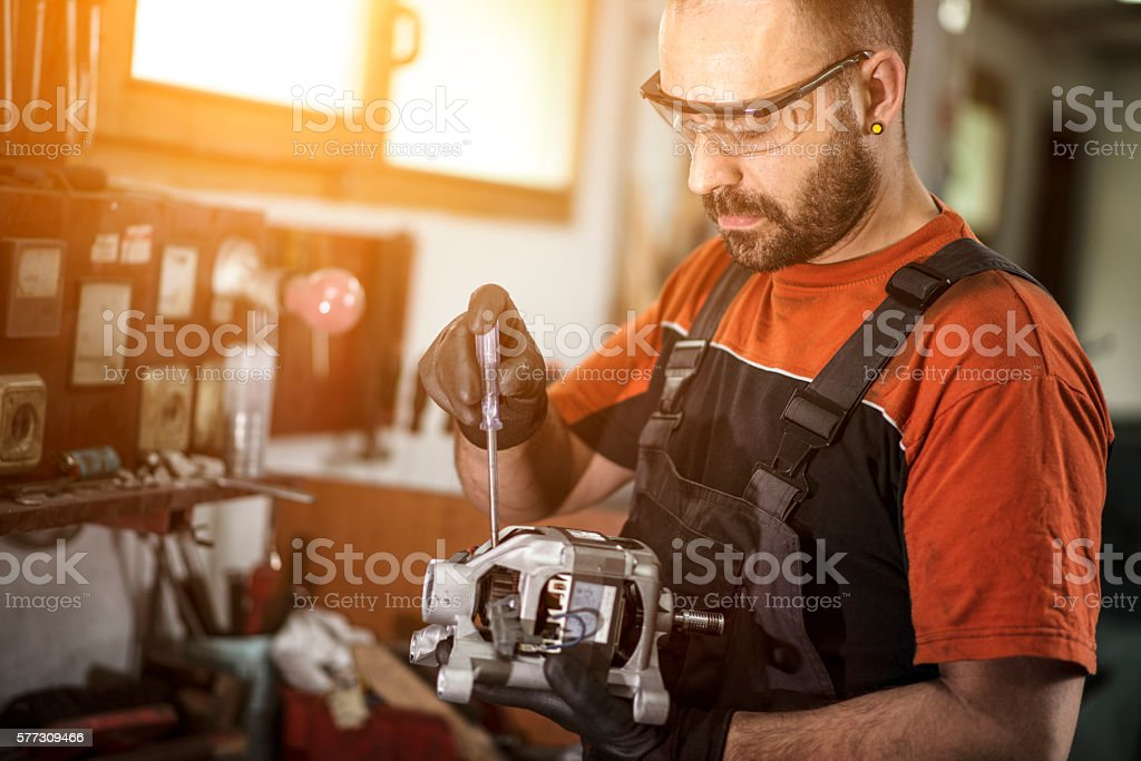 Unrecognizable manual worker working on electric motor stock photo