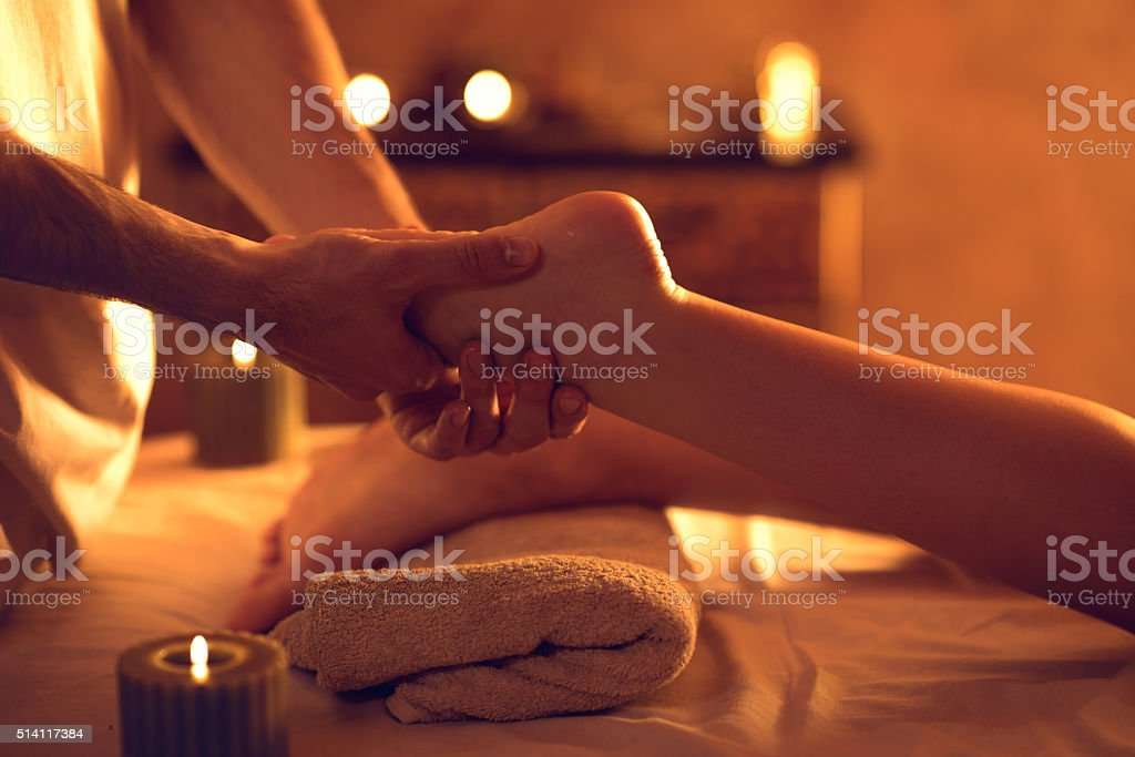 Unrecognizable massage therapist massaging woman's foot at spa. stock photo