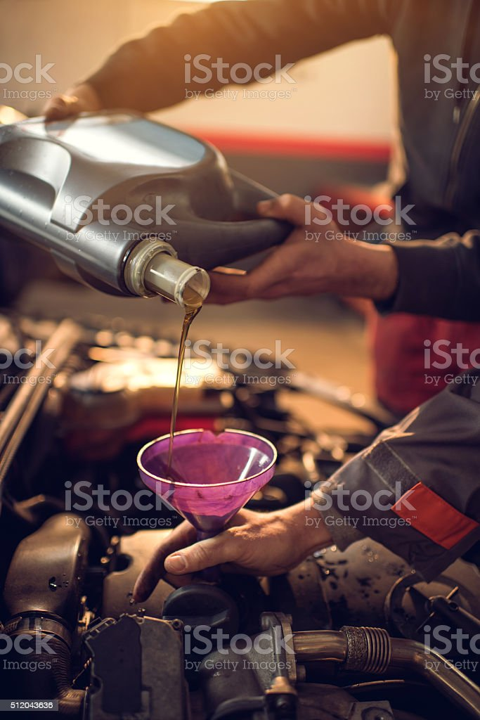 Unrecognizable mechanics pouring an engine oil into the car. stock photo