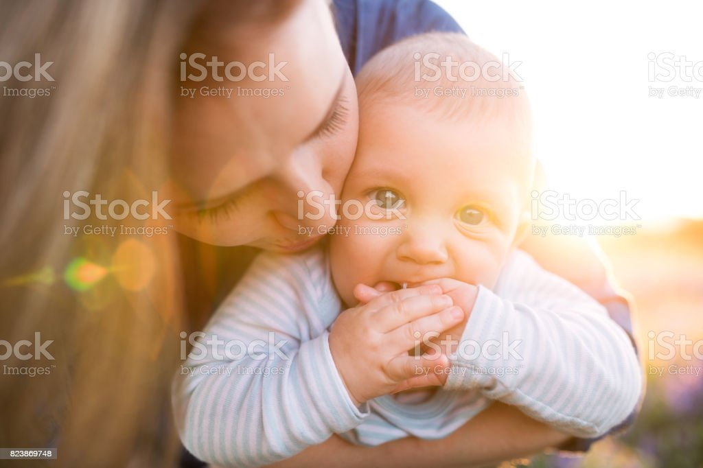 Unrecognizable mother in nature with baby son in the arms. stock photo