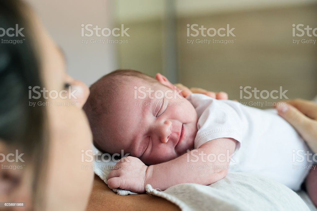Unrecognizable mother with newborn baby son lying in bed stock photo