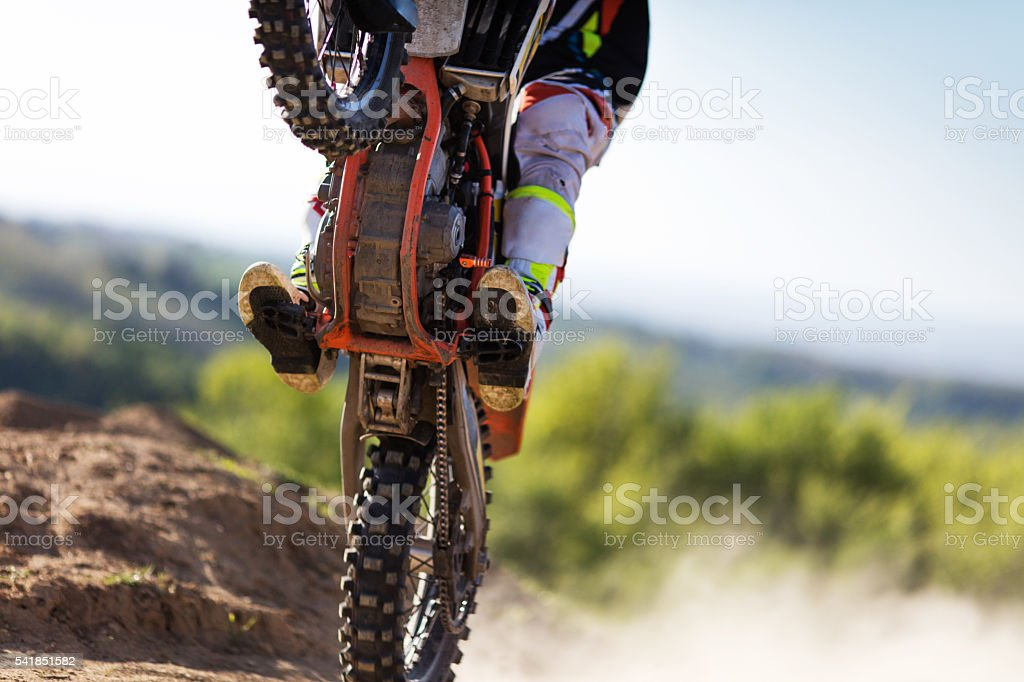 Unrecognizable motocross rider practicing on a dirt road. stock photo