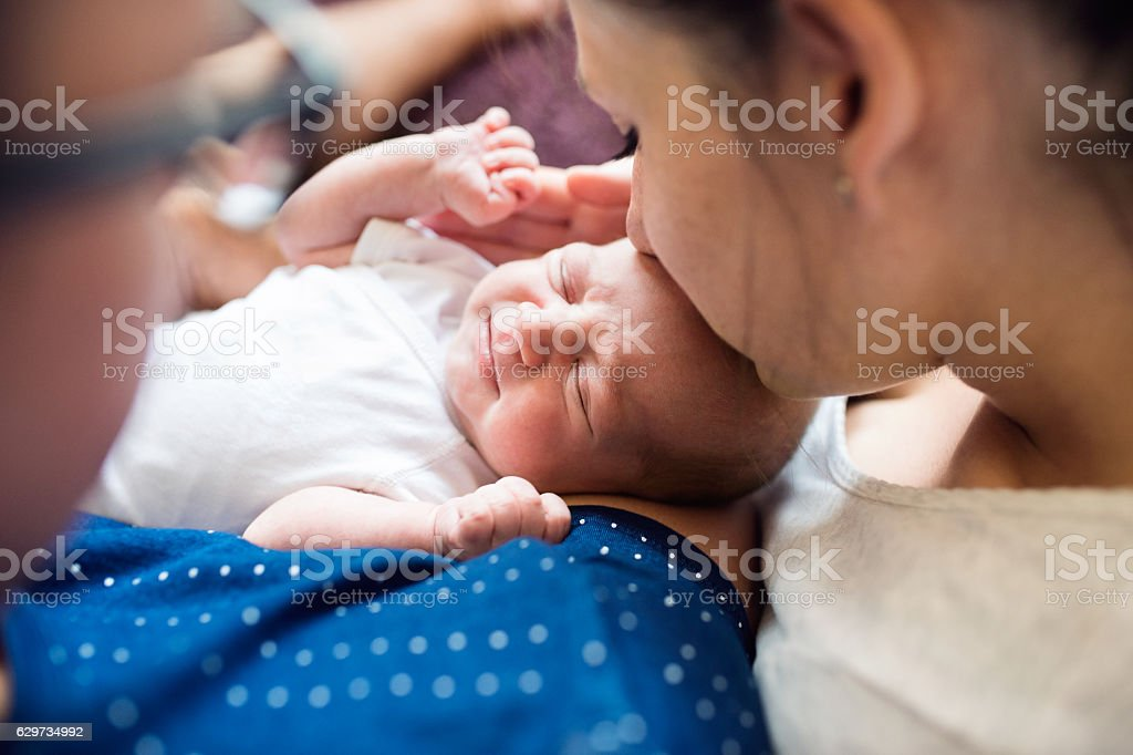 Unrecognizable parents holding their newborn baby son, kissing h stock photo