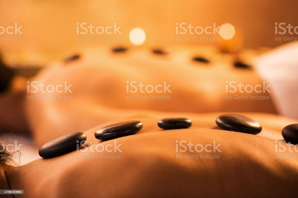 Unrecognizable people receiving hot stone therapy at the spa. stock photo