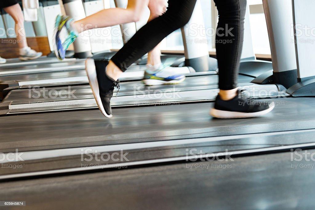 Unrecognizable people running on treadmills stock photo