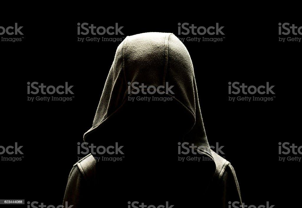 teenage boy standing alone in the dark