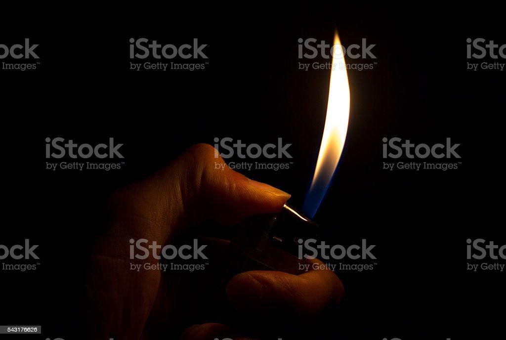 Unrecognizable person igniting cigarette lighter in dark stock photo